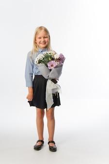Portrait en studio de jolie fille blonde en uniforme scolaire avec beau bouquet cadeau, fond blanc, mise au point sélective