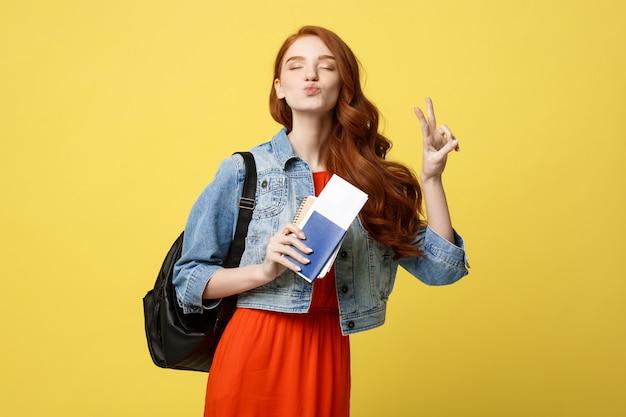 Portrait en studio de pleine longueur de femme jolie jeune étudiante détenant un passeport avec des billets.