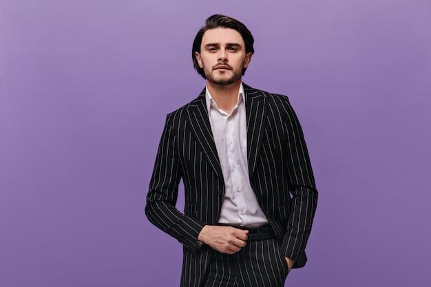 Portrait de style de vie d'un joli jeune homme aux cheveux bruns, barbe et moustache, chemise légère, costume élégant regardant devant et posant contre le mur violet