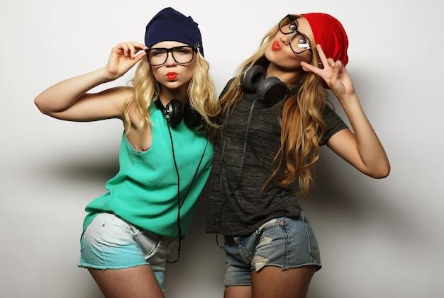 Portrait de style de vie en studio de deux meilleures amies hipster portant des tenues élégantes et lumineuses, des chapeaux, des shorts en jean et des lunettes, devenant folles et s'amusant bien ensemble. jeune et beauté.