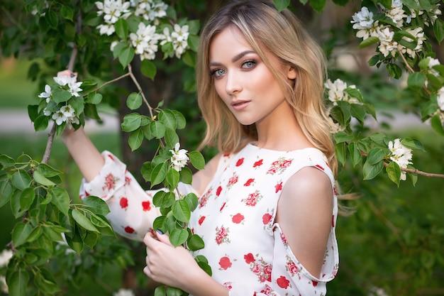 Portrait d'une superbe blonde dans une robe légère dans un jardin d'été ensoleillé en fleurs
