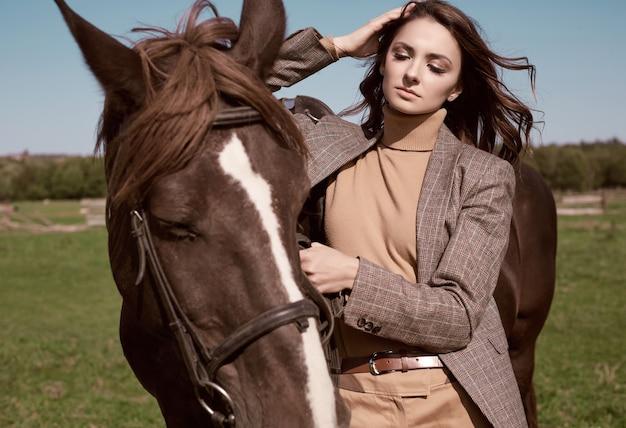 Portrait d'une superbe femme brune dans une élégante veste marron à carreaux posant avec un cheval sur paysage de campagne