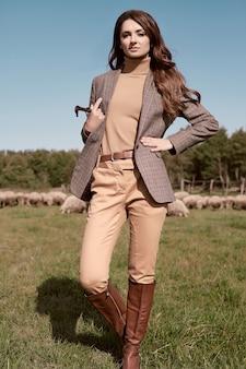 Portrait d'une superbe femme brune dans une élégante veste marron à carreaux posant sur paysage de campagne