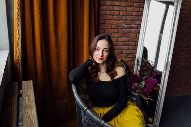 Portrait d'une superbe femme à la mode, assise sur une chaise