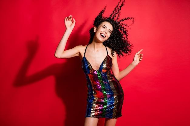 Portrait d'une superbe fille joyeuse et joyeuse aux cheveux ondulés dansant une bachelorette disco isolée sur fond de couleur rouge vif