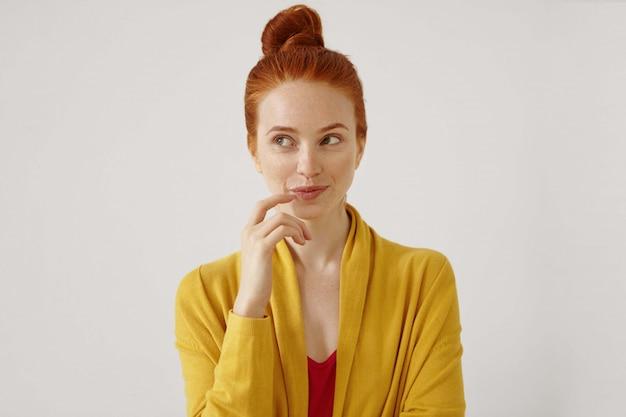 Portrait d'une superbe jeune femme portant ses cheveux roux en noeud touchant les lèvres, détournant les yeux avec un sourire sournois et rusé.