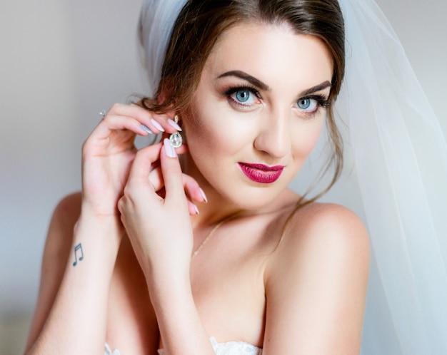 Portrait de superbe mariée avec des lèvres roses foncés et des yeux bleu profond