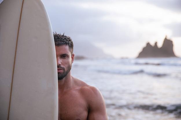 Portrait d'un surfeur couvrant la moitié de son visage avec planche de surf, athlète caucasien musclé à la plage pendant le coucher du soleil. mec attirant avec une barbe.