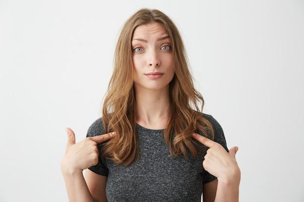 Portrait de surpris belle jeune fille pointant les doigts sur elle-même.