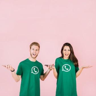 Portrait de surpris jeune homme et femme avec smartphone