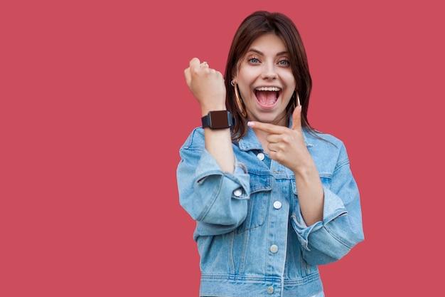 Portrait de surprise heureuse belle jeune femme brune en denim style décontracté debout montrant et pointant sur l'écran de sa montre intelligente avec un visage choqué. tourné en studio, isolé sur fond rouge.