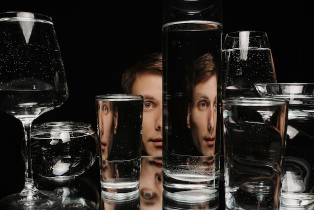 Portrait surréaliste d'un homme regardant à travers des verres d'eau avec reflets et distorsions miroir
