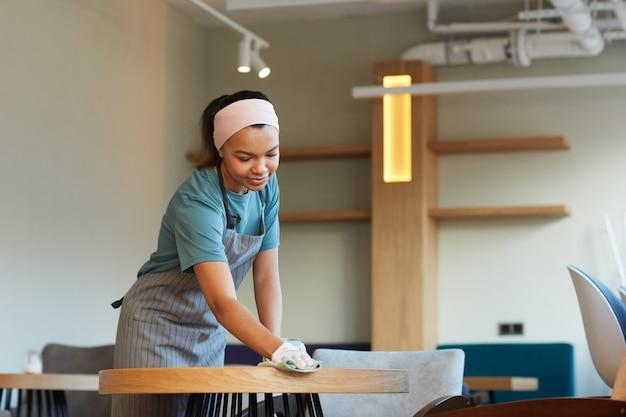 Portrait d'une table de nettoyage de serveuse métisse souriante dans un café ou un café tout en se préparant à l'ouverture le matin, espace de copie