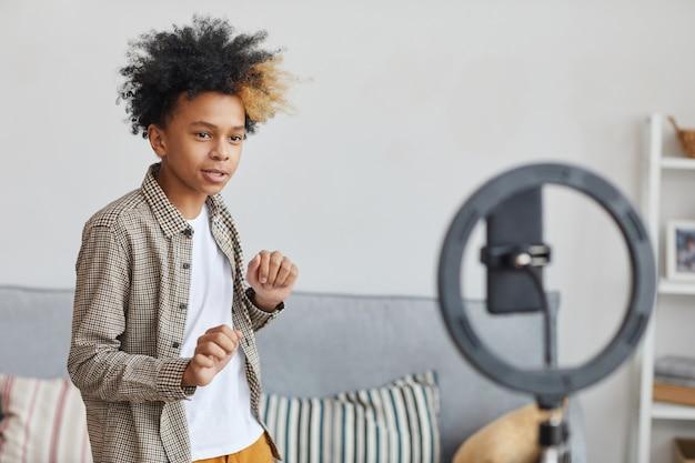 Portrait de taille d'un adolescent afro-américain dansant devant une caméra sur un ringlight à la maison, concept de jeune blogueur, espace de copie
