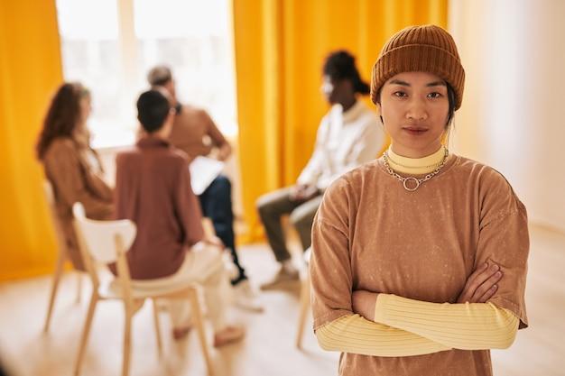 Portrait de taille d'une adolescente asiatique regardant la caméra pendant une séance de thérapie dans un groupe de soutien, espace de copie
