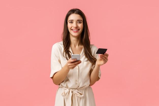 Portrait de taille attrayante, souriante, femme heureuse shoppaholic comme acheter et utiliser des codes promotionnels, trouvé une excellente robe en ligne, tenant une carte de crédit et un téléphone, télécharger l'application de la boutique, mur rose