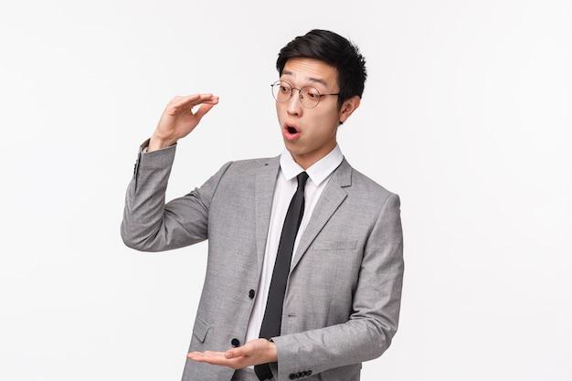 Portrait de taille d'un beau employé de bureau asiatique excité, racontant au client de grandes opportunités de revenus, décrivant un projet façonnant un gros objet, une grosse somme d'argent, l'air étonné
