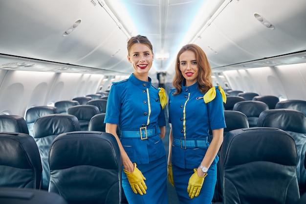 Portrait de taille de charmantes femmes hôtesses de l'air en uniforme bleu posant et regardant l'appareil photo au tableau