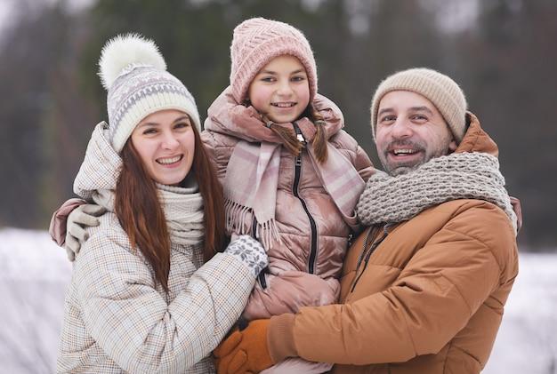 Portrait de taille d'un couple adulte heureux tenant sa fille et souriant à la caméra tout en profitant d'une promenade en plein air ensemble dans la forêt d'hiver