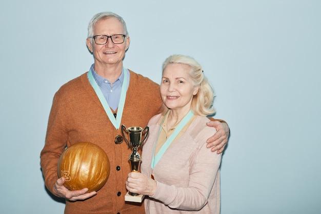 Portrait de taille d'un couple de personnes âgées souriant tenant un trophée et des boules de bowling en se tenant debout sur fond bleu, tourné avec flash, espace pour copie