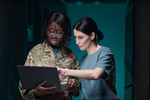 Portrait de taille de deux femmes portant un uniforme militaire utilisant un ordinateur portable tout en se tenant dans la salle des serveurs, espace de copie