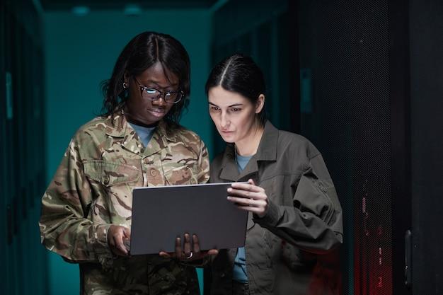 Portrait de taille de deux jeunes femmes portant un uniforme militaire utilisant un ordinateur portable tout en se tenant dans la salle des serveurs, espace de copie