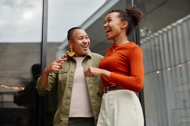 Portrait de taille de deux jeunes femmes riant d'un blanc insouciant profitant d'une fête en plein air sur le toit
