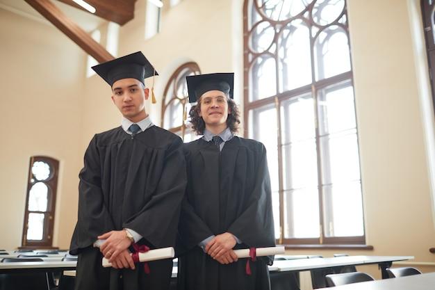 Portrait de taille de deux jeunes hommes portant des robes de graduation et regardant la caméra en se tenant debout dans l'auditorium de l'école, espace pour copie