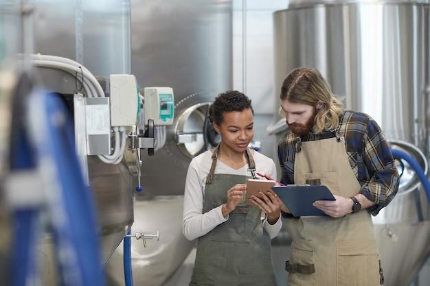 Portrait de taille de deux jeunes travailleurs utilisant une tablette numérique tout en inspectant la production dans une brasserie artisanale moderne, espace de copie
