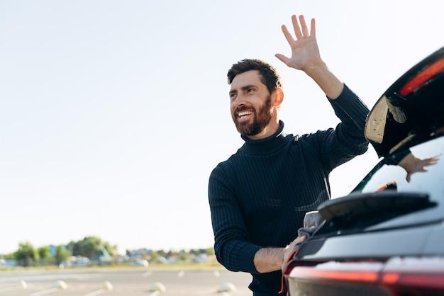 Portrait de taille du bel homme caucasien tenant la microfibre à la main et polissant la voiture tout en saluant quelqu'un dans la rue