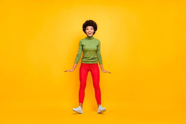 Portrait de la taille du corps pleine longueur de joyeuse positive jolie jolie femme en pantalon rouge baskets blanches sourire à pleines dents retombant avec le vent qui souffle.