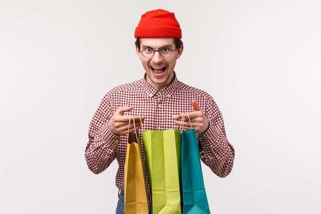 Portrait de taille excité drôle jeune homme avec barbe, porter un bonnet et des lunettes, rire rusé et heureux, ouvrir les sacs à provisions, recevoir des cadeaux impressionnants,