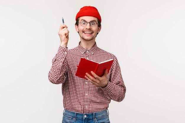 Portrait de taille excité et ravi jeune homme frappé avec une idée géniale, dites eureka et soulevez le stylo avec un sourire inspiré satisfait, tenant un cahier, résolvant une équation difficile,