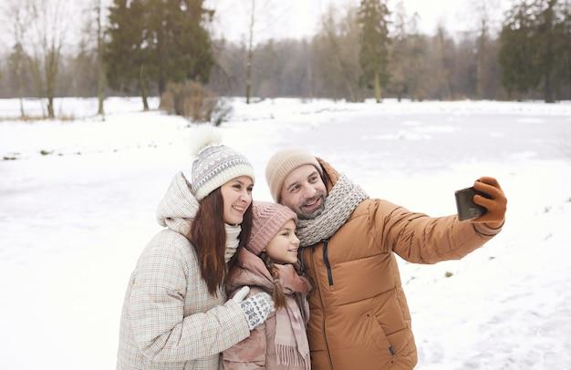 Portrait de taille d'une famille heureuse prenant une photo de selfie tout en profitant d'une promenade en plein air ensemble dans la forêt d'hiver, espace de copie