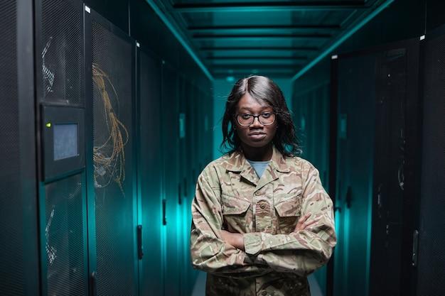 Portrait de taille d'une femme afro-américaine dure regardant la caméra en se tenant debout dans la salle des serveurs avec un arrière-plan futuriste, espace pour copie