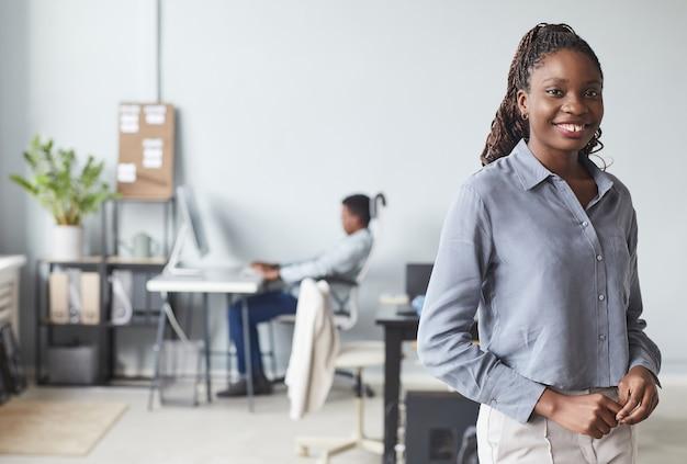 Portrait de taille d'une femme afro-américaine réussie souriant à la caméra tout en posant à l'intérieur du bureau, espace pour copie