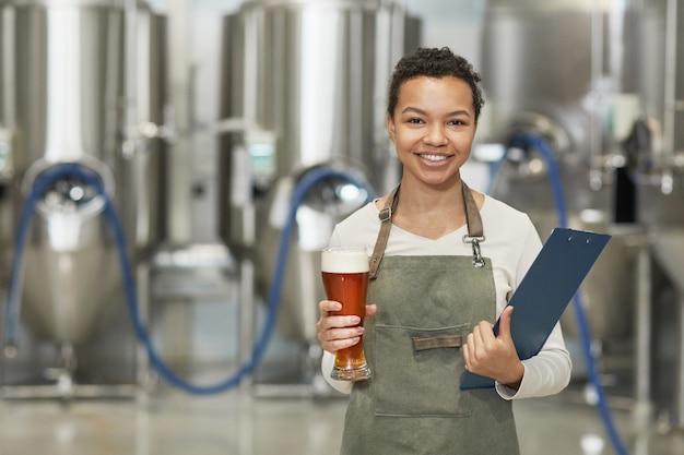 Portrait de taille d'une femme afro-américaine souriante tenant un verre à bière et regardant la caméra en se tenant debout dans l'atelier de l'usine de brassage, espace pour copie