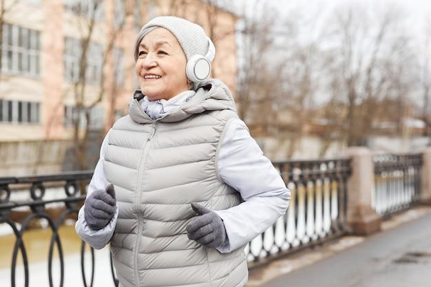 Portrait de taille d'une femme âgée active qui court à l'extérieur en hiver et souriant joyeusement, espace pour copie