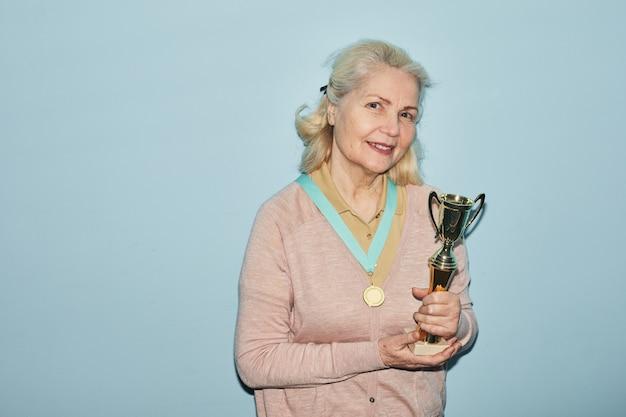 Portrait de taille d'une femme âgée souriante tenant un trophée et regardant la caméra en se tenant debout sur fond bleu, espace pour copie