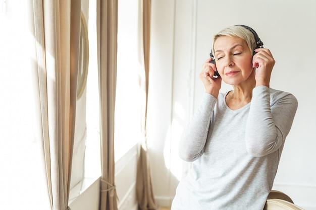 Portrait de taille d'une femme âgée, les yeux fermés, écoutant de la musique dans les écouteurs