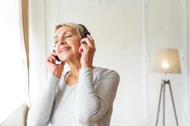 Portrait de taille d'une femme caucasienne senior souriante dans les écouteurs, profitant de sa musique préférée
