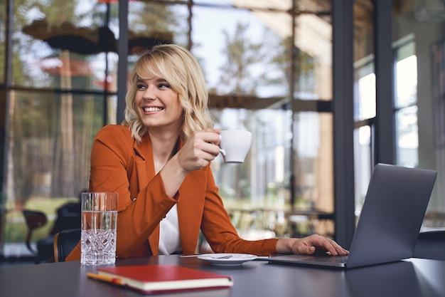 Portrait de taille d'une femme entrepreneur souriante assise avec une tasse de café à la table