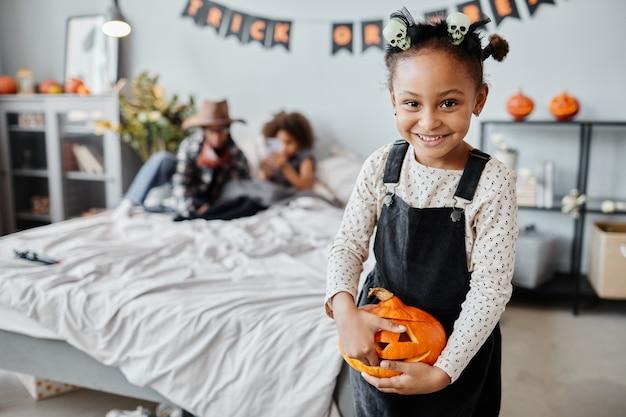 Portrait à la taille d'une fille afro-américaine heureuse tenant une citrouille sculptée et souriant à la caméra pendant que s...