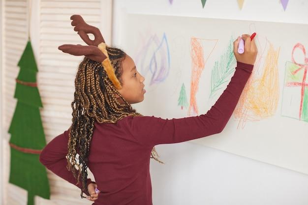 Portrait de taille de fille afro-américaine portant des bois de cerf et dessin sur les murs tout en profitant de cours d'art à noël, espace copie