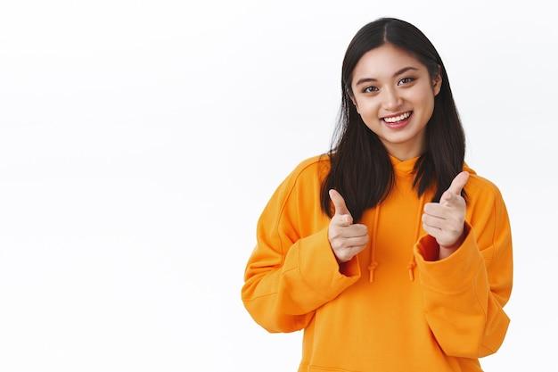 Portrait de taille fille asiatique brune joyeuse en sweat à capuche orange, montrant le pouce levé et souriant heureux, hoche la tête en signe d'approbation, debout près d'un espace blanc clair pour votre promo, comme ça