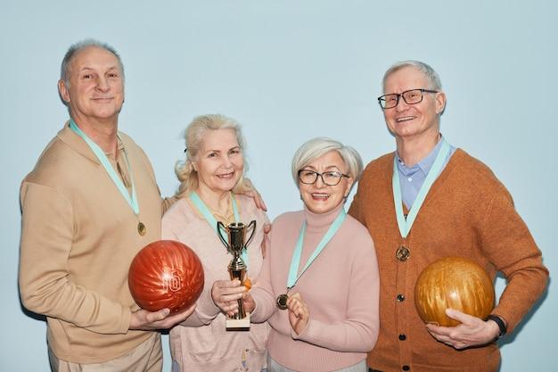 Portrait de taille d'un groupe de personnes âgées tenant un trophée et des boules de bowling en se tenant debout sur fond bleu, tourné avec flash