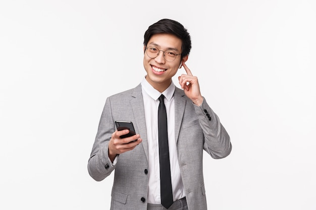 Portrait de taille d'homme d'affaires asiatique heureux, souriant heureux dans des écouteurs sans fil, tenant un téléphone mobile, changer le volume ou appeler quelqu'un sur des écouteurs, debout sur un mur blanc