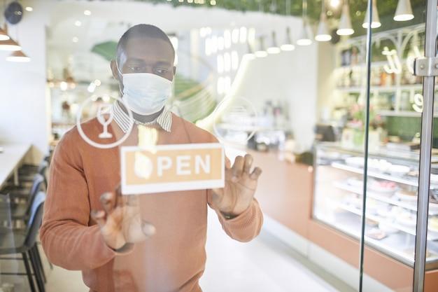 Portrait de taille d'un homme afro-américain portant un masque tout en accrochant un panneau ouvert sur la porte vitrée du café le matin, espace pour copie