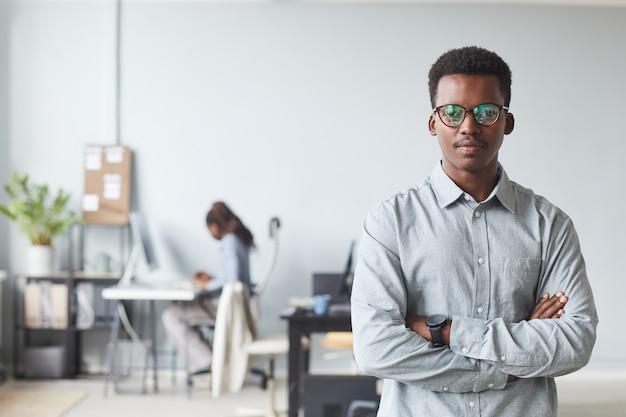 Portrait de taille d'un homme afro-américain réussi regardant la caméra en se tenant debout, les bras croisés au bureau, espace pour copie
