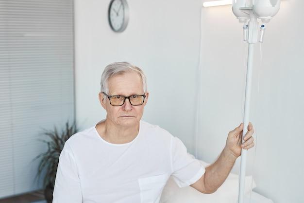 Portrait de taille d'un homme âgé dans une chambre d'hôpital tenant un support d'injection intraveineuse et regardant la caméra, espace de copie